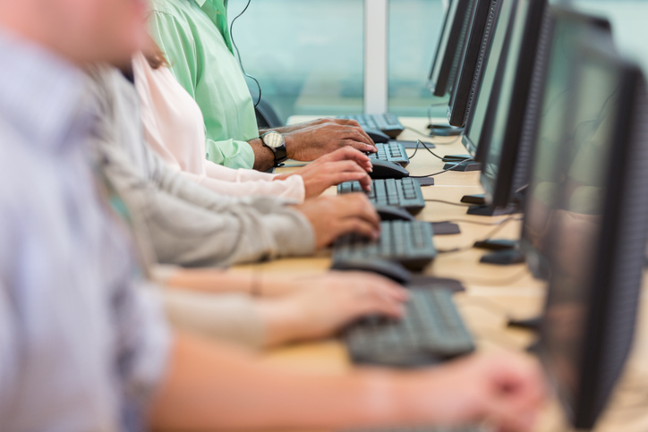 Row of diverse people typing on keyboards while working in a call center.